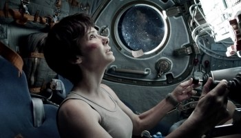 Gravity's Dr. Ryan Stone (Sandra Bullock) takes respite in a Soyuz (Credits: Warner Bros.).