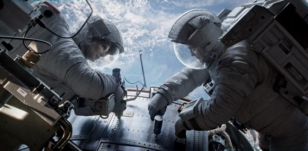 """Gravity"" astronauts Ryan Stone (Sandra Bullock) and Matt Kowalski (George Clooney) repair the Hubble Space Telescope (Credits: Warner Bros.)."