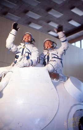 Commander Vyacheslav Zudov (left) and Flight Engineer Valeri Rozhdestvensky, clad in their pressure suits, are pictured with a Soyuz mockup during training. Photo (Credits: Joachim Becker / SpaceFacts.de).