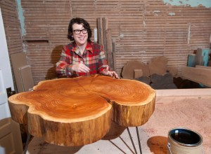 Adriene Wicks, co-owner of Birdloft, varnishes a Nimbus Cloud Coffee Table at her workshop