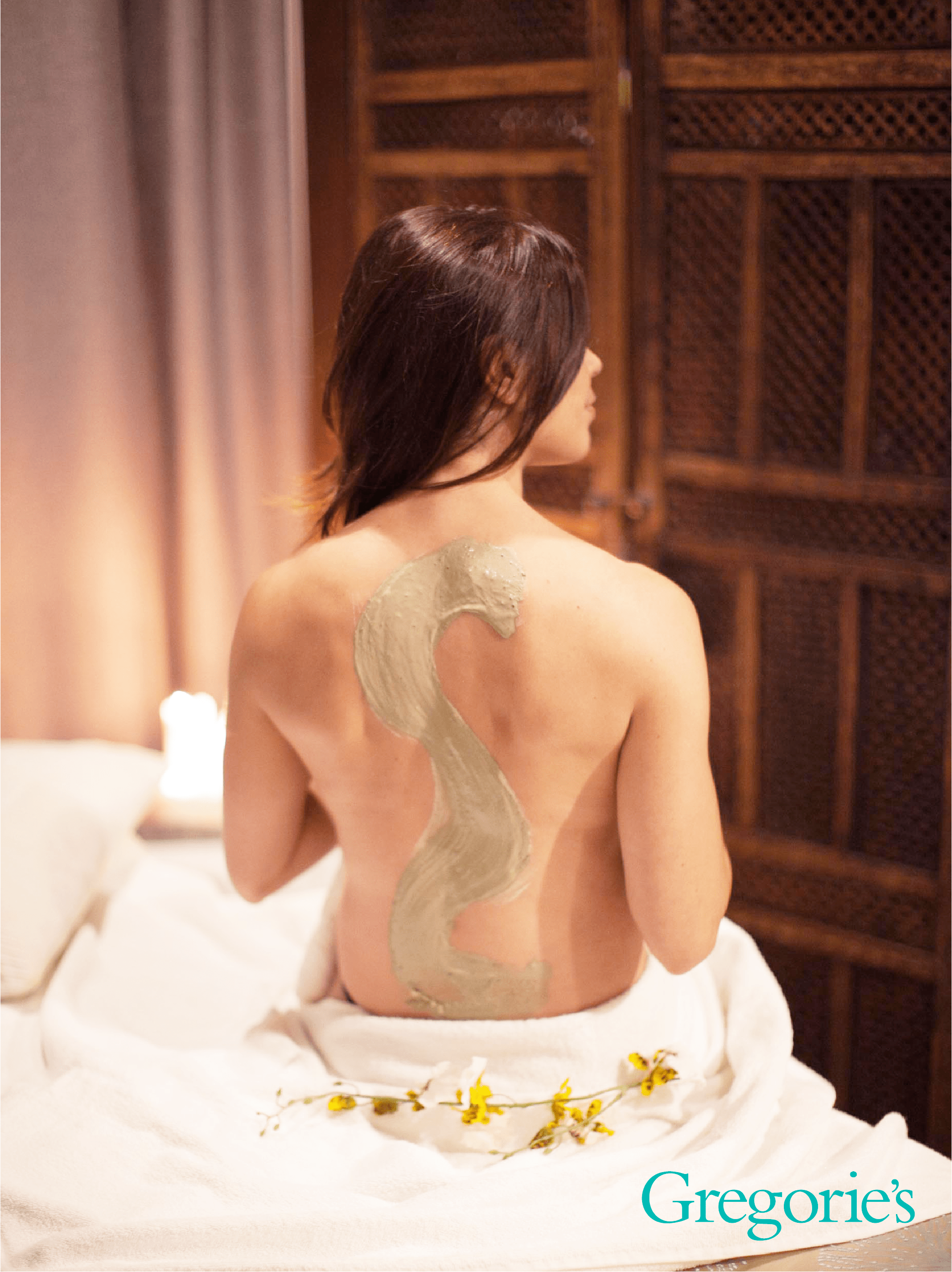 Woman sitting on massage table with mask on her back. Example of a body treatment.
