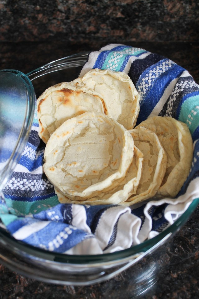 Fresh made sope shells cooling on a dish towel in a shallow baking dish.