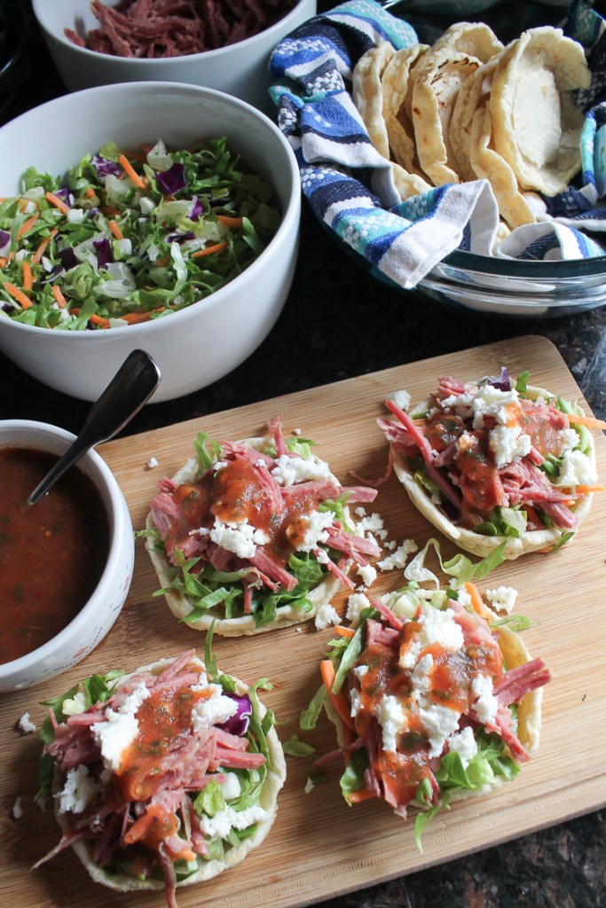 Homemade sopes shells with chopped lettuce, slow-cooked shredded corned beef, queso fresco and red salsa.