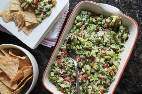 Large batch of ceviche served in a baking dish with tortilla chips on the side.