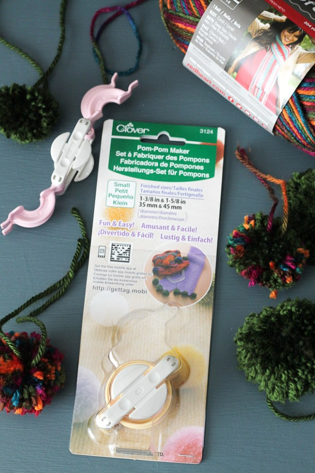 Pom Pom maker, pom poms, and a ball of yarn.