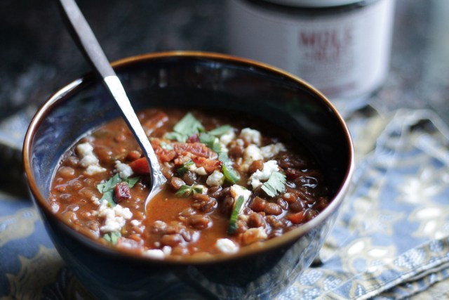 Dark blue and brown bowl with lentil soup, topped with bacon bits, cheese, and cilantro, spoon in soup.