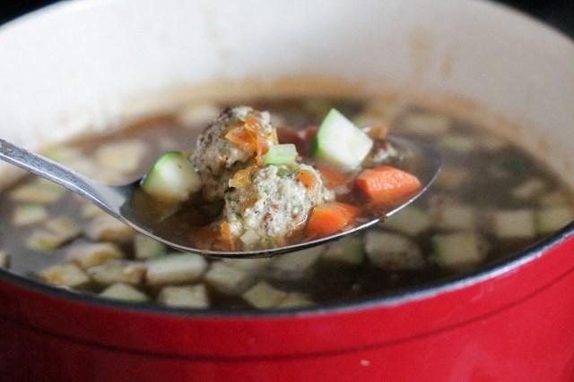 Turkey meatballs soup in a serving spoon.