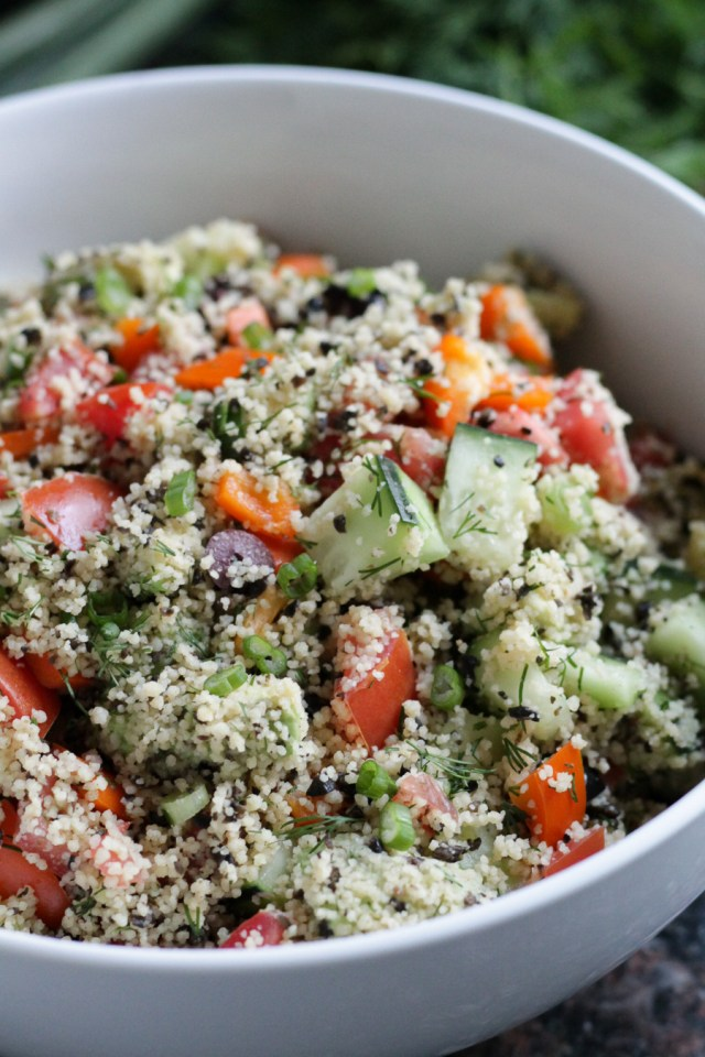 Couscous garden salad served in a large white serving bowl