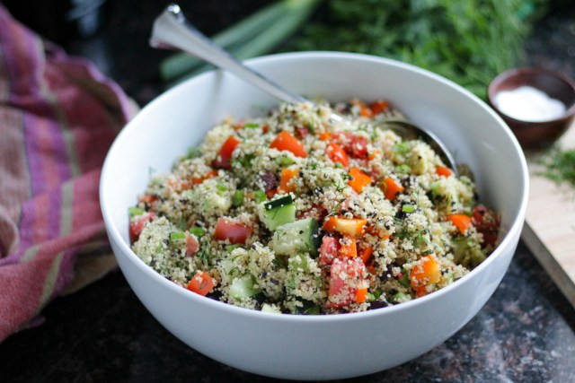 Couscous mixed with chopped vegetables served in a white serving bowl.