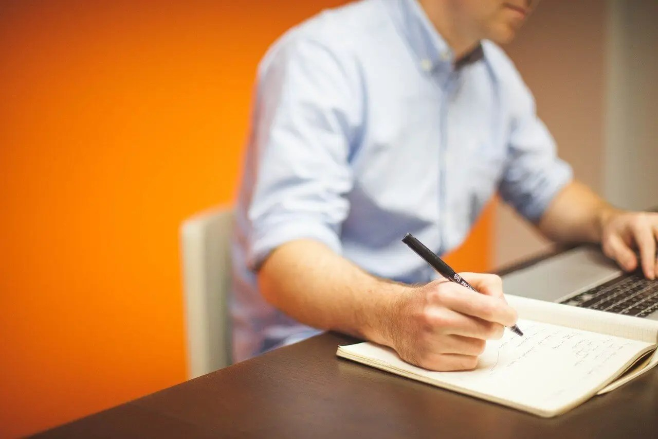 Male half body writing a note on a desk