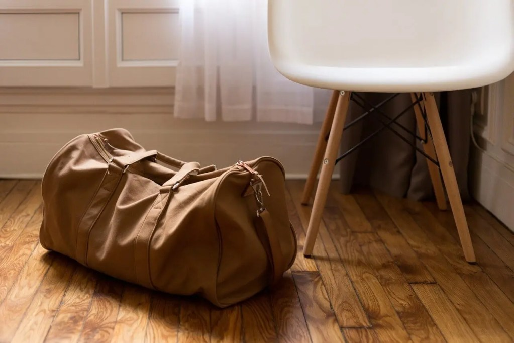 Brown bag next to a chair on a wood floor