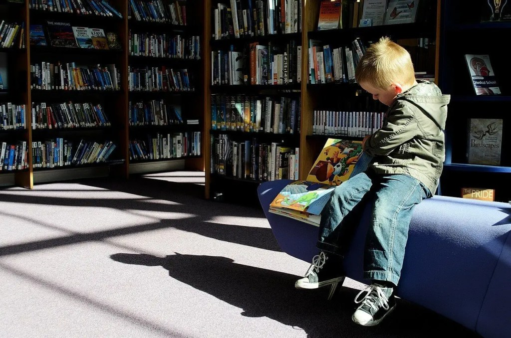 Kid in a library opening a book