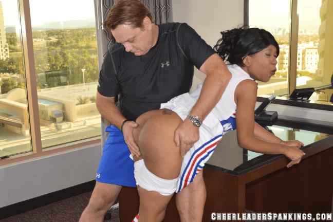 Ebony cheerleader Cupcake is spanked over the desk on her bare bottom