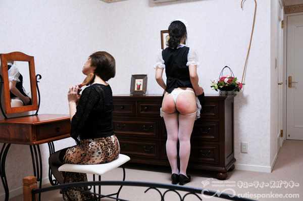 Japanese maid faces the wall with her red bottom on display after spanking