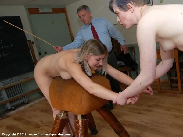 Big-boobed Belinda Lawson is given a nude caning with her wrists held in place by Helen Stephens