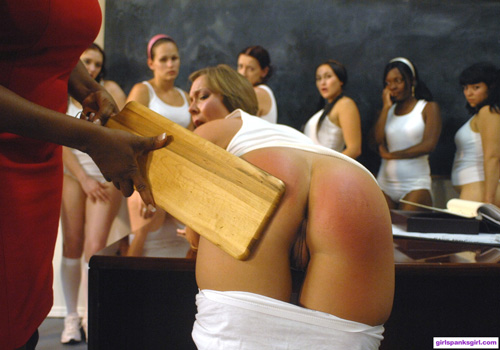 Julie Night bends over for the wooden paddle while the others watch from the front of class