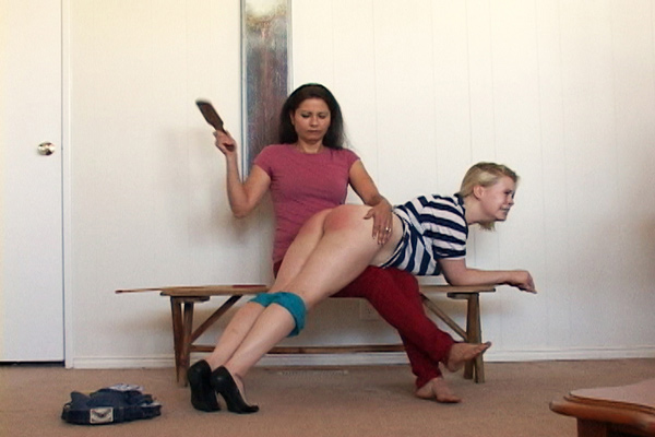 Chelsea Pfeiffer paddles Stevie Rose's bare bottom with an uncompromising wooden paddle