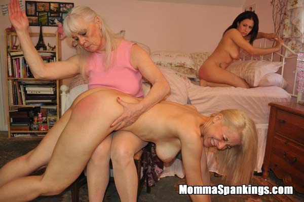 The two naked girlfriends are spanked on the edge of Sarah's bed by strict Momma