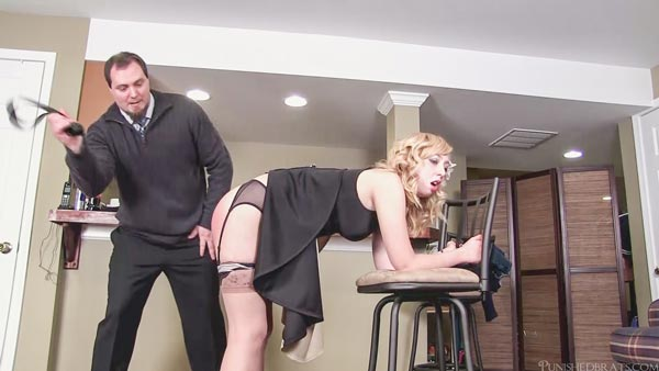 Mandie Rae bending over and about to get a whack of the strap on her bare bottom