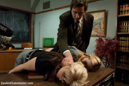 Professor, Sarah Vandella, and student, Emma Haize are made to bend over the desk side-by-side as the dean punishes them
