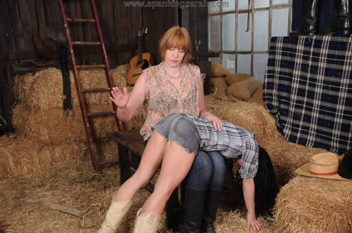 Sarah pulls Kiki straight over her knee for a spanking over her denim shorts