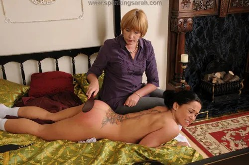 Kiki gets her firm, round bottom spanked by Sarah's paddle
