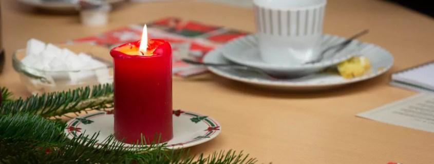 Weihnachtliche Kerze und eine Tasse auf einem Tisch