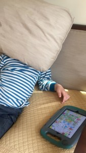 AuthenticAAC moment with the student slouching on a sofa next to his AAC device covering his face with a pillow.