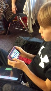 Owen looking at his vocabulary on the Speak for Yourself AAC app on an iPhone for the first time.