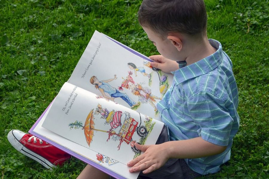 young boy sitting on the grass and looking at a kids book