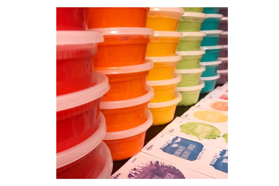 Many stacked jars of colourful play dough
