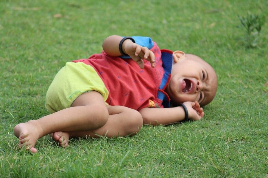 child lying on the grass crying