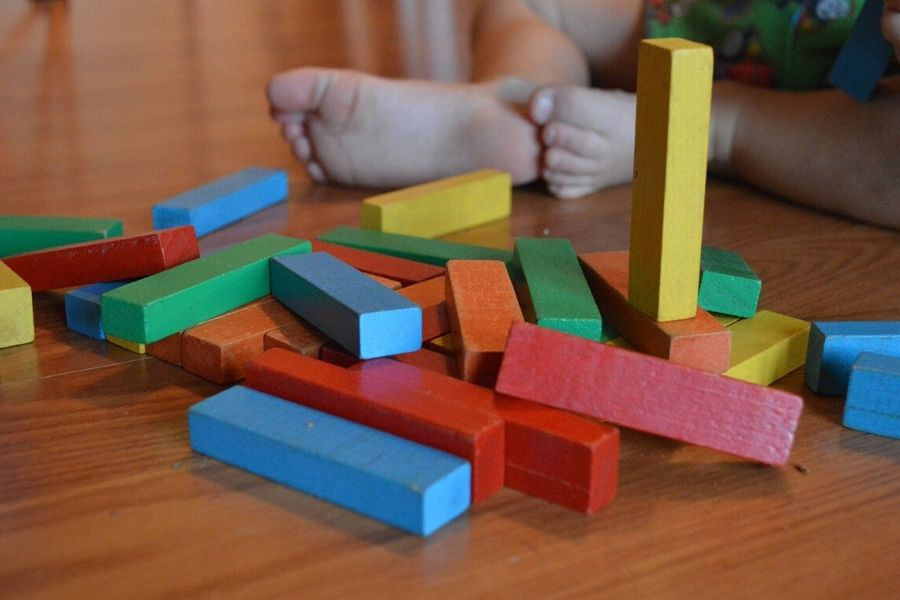 rotate toys - child sitting in front of lots of colourful wooden blocks