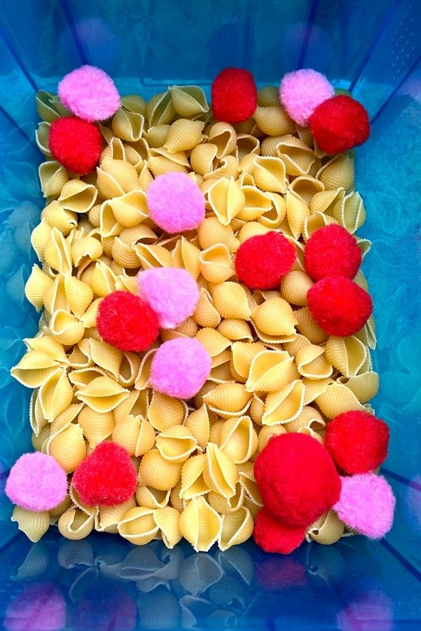 a blue box with dried pasta and red and pink pompoms