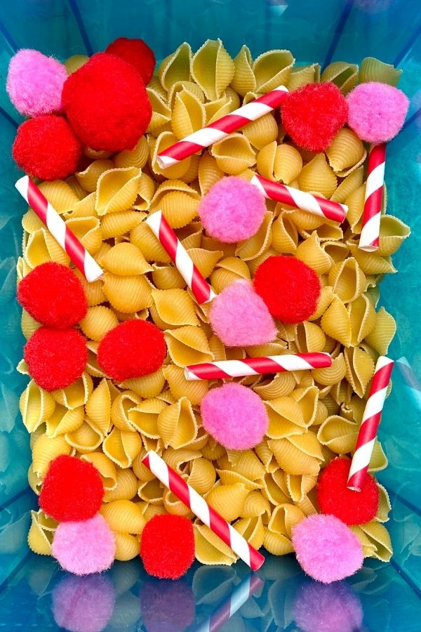 blue sensory bin with red and pink pompoms, dried pasta and white and red paper straws