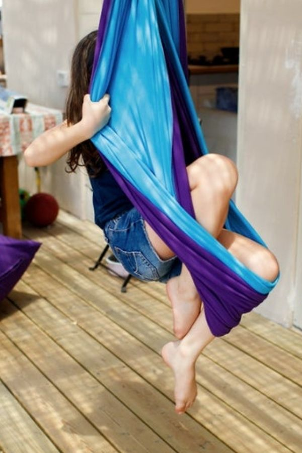 child sitting in a cotton and lycra autism sensory swing