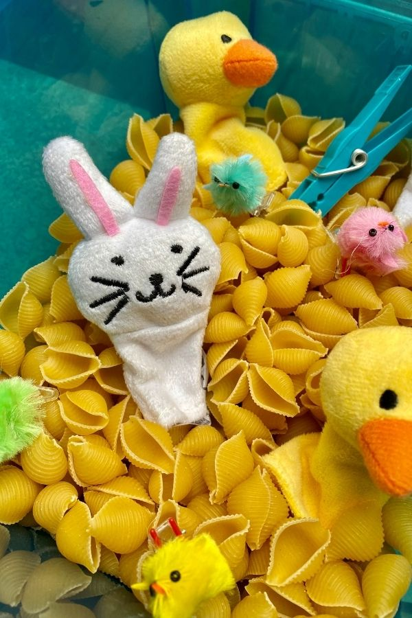 a bunny finger puppet in a pasta sensory box
