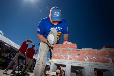 Juan Cabral placing the first brick of his third row