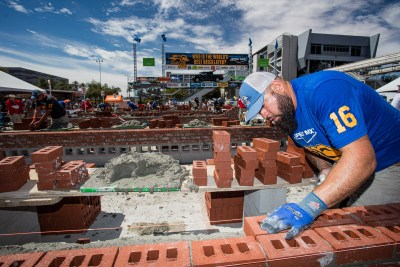 David Puga making sure the brick is in the perfect position on his wall
