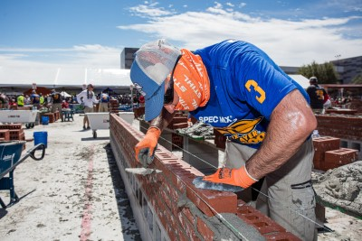 Esteban Cabral trying to avoid getting sunburned while working his wall