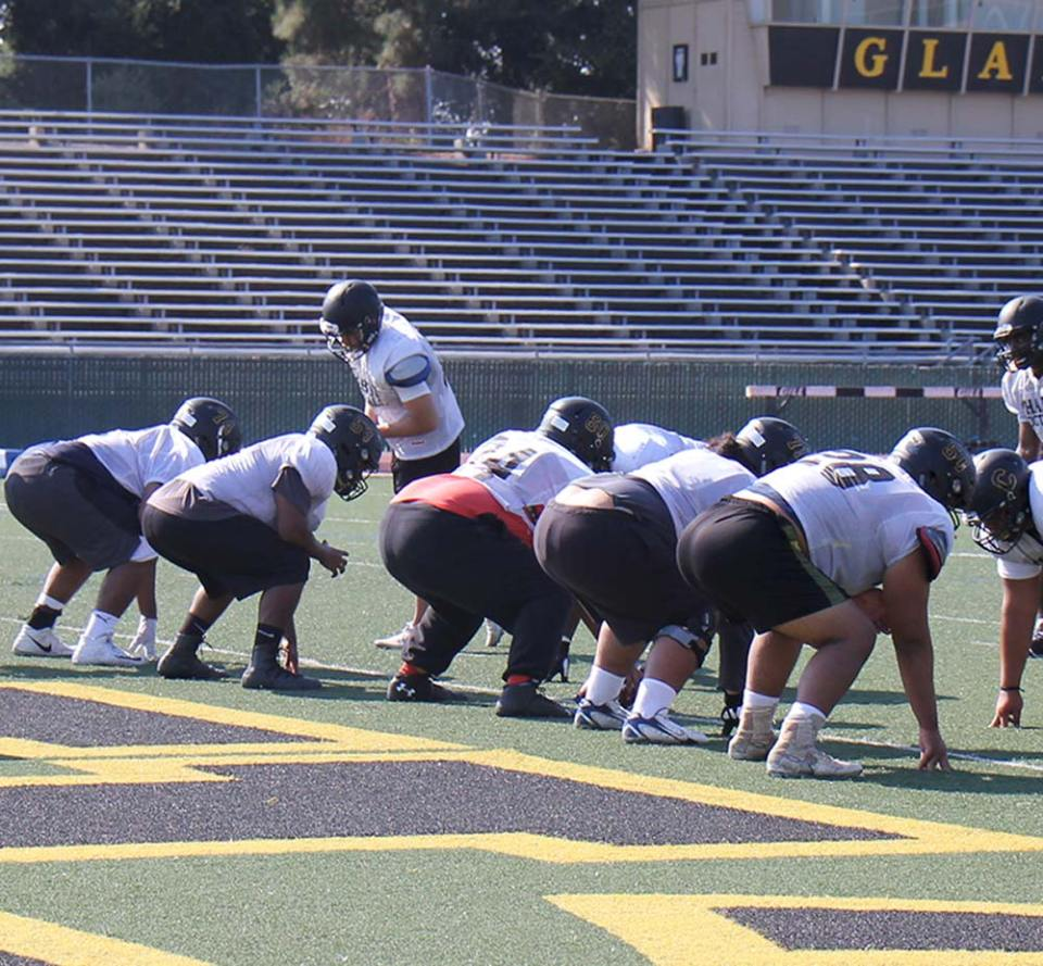 Chabot Gladiators Football team practicing on football field as a scrimmage wearing helmets, pads, jerseys, and shorts.
