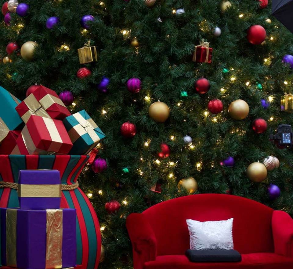 A decorated Christmas tree with a big bag of decorative Christmas presents as well as a big chair for Santa to sit in for pictures