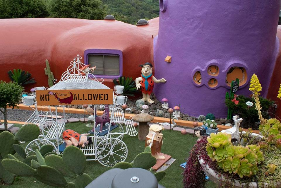 Orange and purple doomed house with decorations of bread flintstone