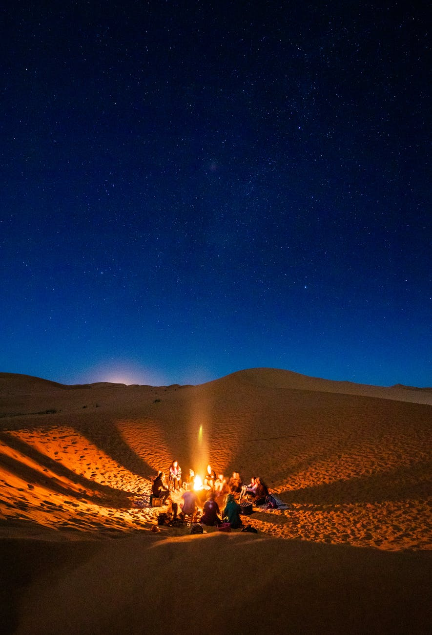 Moroccan people sitting in front of bonfire in desert during nighttime in Morocco