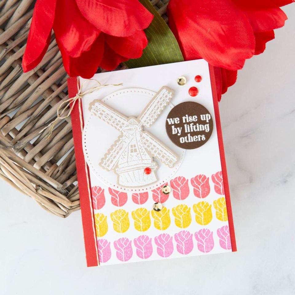 We Rise By Lifting Others crisp and bright handmade card with pink, red, and yellow stamped tulips and beautiful Dutch windmill embossed in white. #funstampersjourney #cardmaking