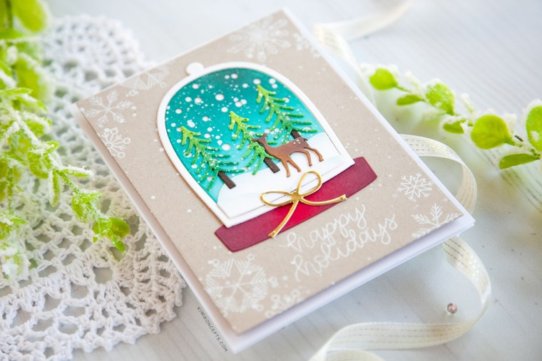 "Spellbinders Holiday 2019 Inspiration | Clean & Simple Christmas Cards with Keeway Tsao. Keeway says: ""This card showcases the Shapeabilities Santa's Workshop dies. This die creates a beautiful little scene within a snow globe. I started by die cutting the snow globe frame and backing which was then ink blended with Peacock Feathers and Tumbled Glass distress oxide inks."""