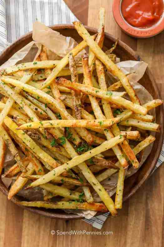 A wooden bowl full of homemade oven baked french fries with ketchup.