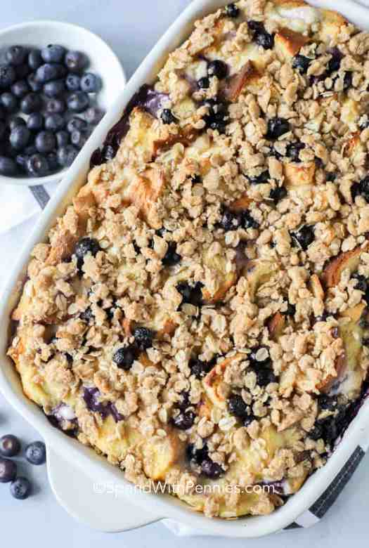 A top photo of overnight french toast bake in a white baking dish with fresh blueberries on the side.