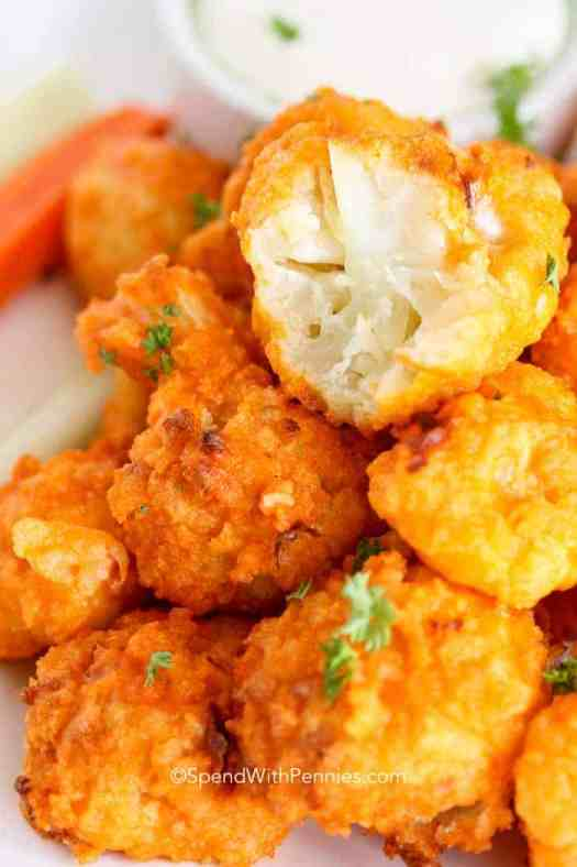 A pile of baked buffalo cauliflower bites with a bite taken out of one.