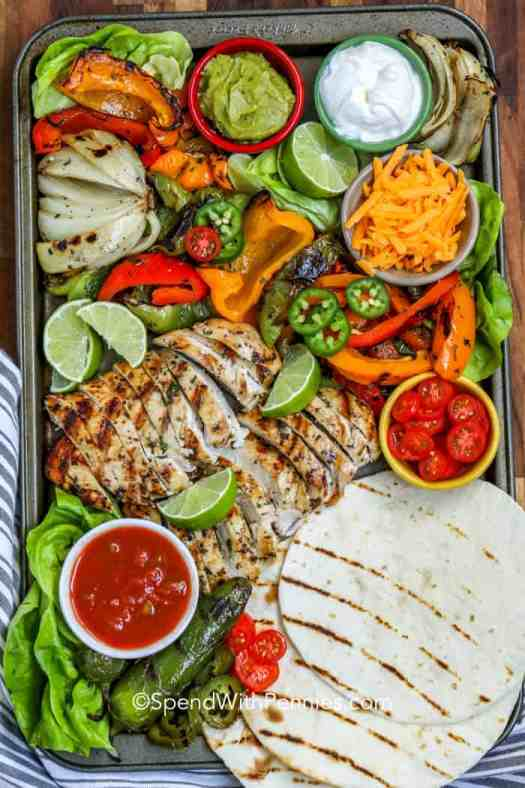A pan of grilled chicken fajitas with a spread of toppings ready to serve.